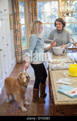 Young woman treating dog whist baking with grandmother - Stock Photo