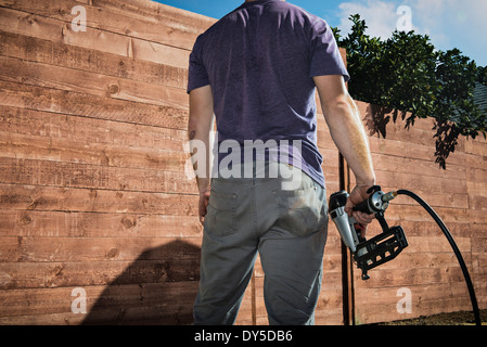 Cropped shot of joiner in backyard in front of new fence - Stock Photo