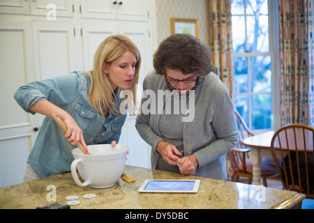 Senior woman and granddaughter baking and using digital tablet - Stock Photo
