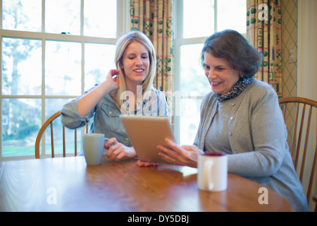 Senior woman and granddaughter looking at digital tablet - Stock Photo