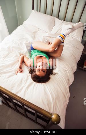 Young woman lying on bed, high angle - Stock Photo