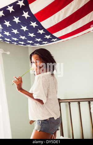 Young woman holding rose with US flag - Stock Photo