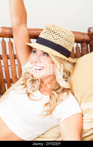 Young woman wearing straw hat looking up - Stock Photo