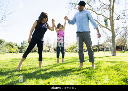 Mid adult couple lifting up young daughter in park