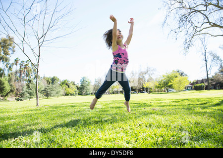 Young girl jumping mid air in park - Stock Photo