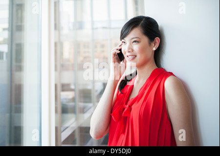 Young businesswoman chatting on cellphone in office - Stock Photo