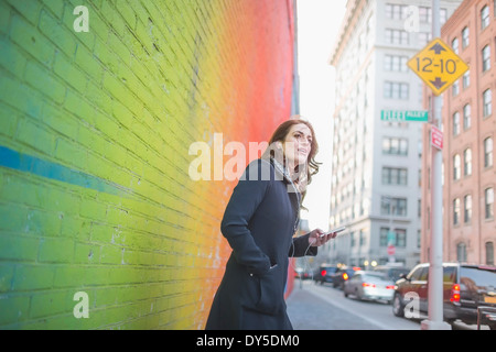 Young woman waiting on city street - Stock Photo