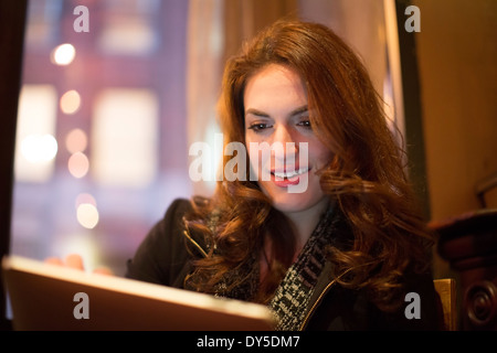 Young woman using digital tablet in cafe - Stock Photo