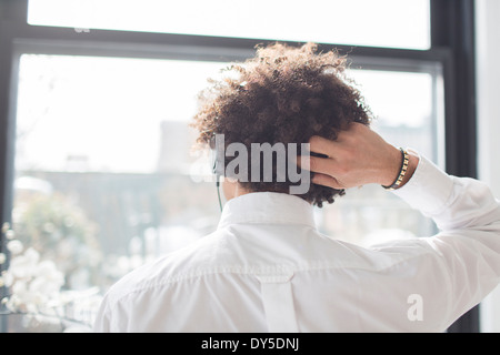 Young man scratching head, rear view - Stock Photo