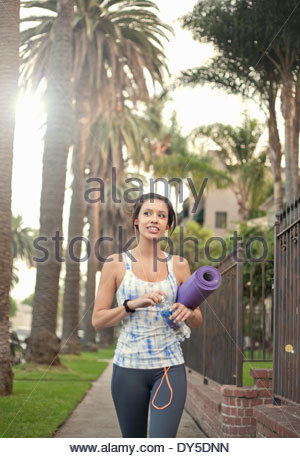 Young woman walking along sidewalk carrying yoga mat - Stock Photo