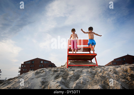 Two boys jumping off red notice board, Long Beach, New York State, USA - Stock Photo