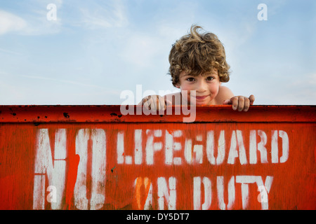 Portrait of boy and lifeguard sign, Long Beach, New York State, USA - Stock Photo
