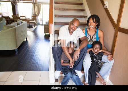Portrait of mature couple with son and daughter on stairs - Stock Photo