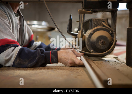 Close up of man using radial arm saw in workshop - Stock Photo