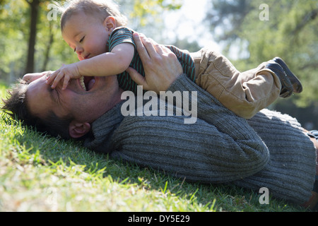 Father and son playing on grass - Stock Photo