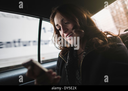 Young woman looking at cellphone in taxi - Stock Photo