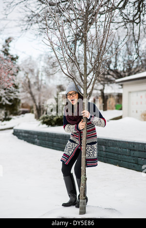 Young woman holding onto tree in slippy snow