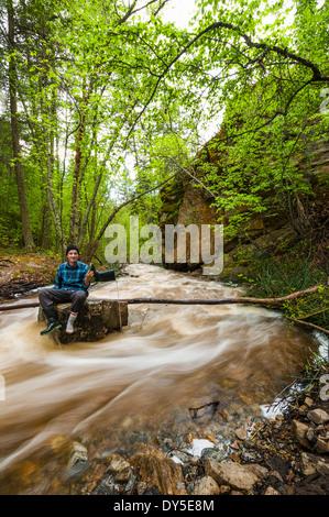 Male hiker sitting on flooded river rock, Naramata, British Columbia, Canada - Stock Photo
