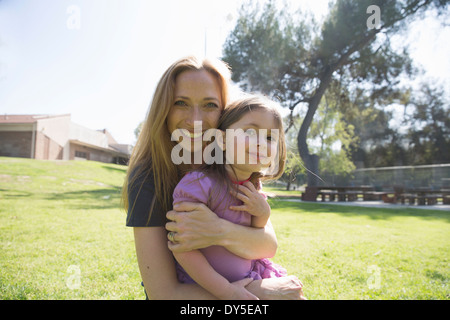 Mother hugging daughter in park - Stock Photo