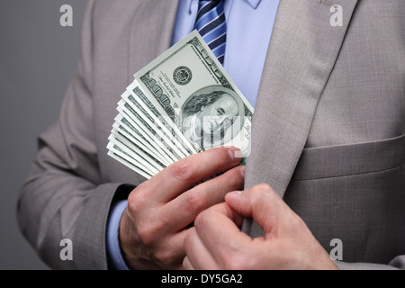 Businessman putting money in pocket - Stock Photo