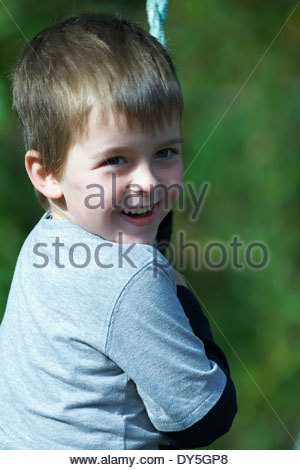 A small boy with brown hair, wearing a grey shirt and smiling; he is holding the rope of a preschool swing. A blurred - Stock Photo