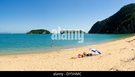 Young women sun on Tata Beach, Tata Bay, near Takaka, New Zealand - Stock Photo