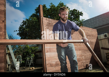 Joiner in backyard lifting wood framework - Stock Photo