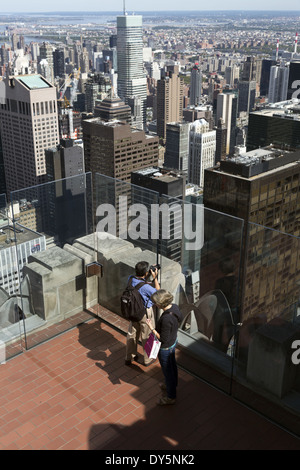 Man photographing New York City from top of Rockefeller Center Observation Deck - Stock Photo