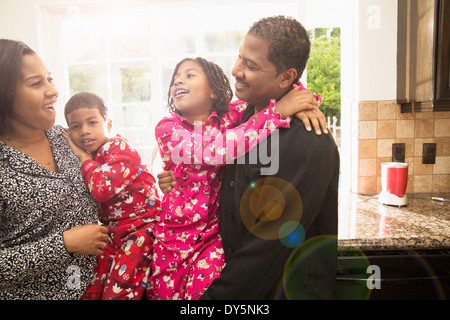 Mid adult couple and children in kitchen - Stock Photo
