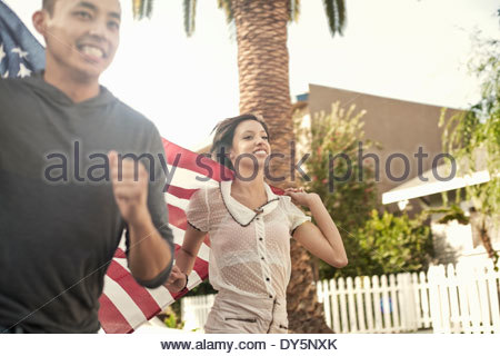 Couple running along street holding up the American flag - Stock Photo