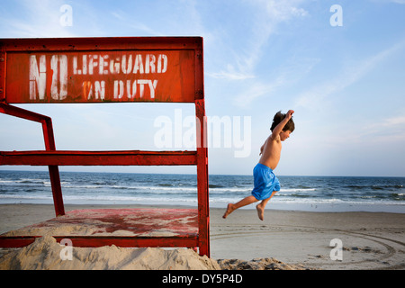 Boys jumping mid air, Long Beach, New York State, USA - Stock Photo