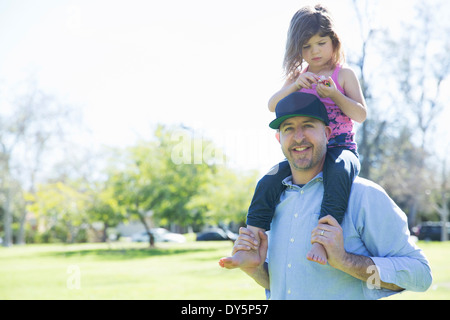 Portrait of mid adult man with young daughter on his shoulders - Stock Photo