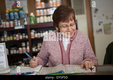 Health foods store owner doing paperwork - Stock Photo