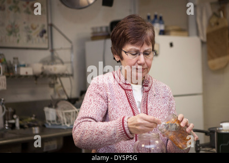 Health foods store owner putting herbs in jars - Stock Photo