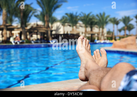 Sunbathing by swimming pool - Stock Photo