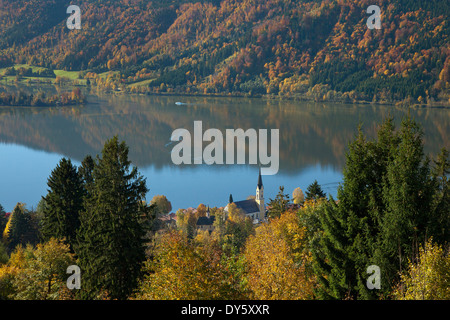 View over autumnal trees onto the church at lake Schliersee, Upper Bavaria, Germany, Europe - Stock Photo