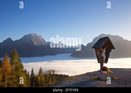 Wayside cross, view over the fog in the valley onto Watzmann and Hochkalter, Berchtesgaden region, Berchtesgaden - Stock Photo
