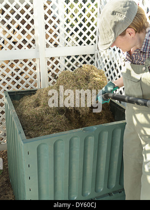 Female gardener turning over compost bin content using pitchfork to speed up decomposting process - Stock Photo
