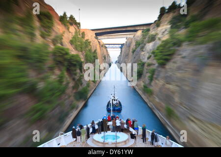 Tourists on the bow of a small cruise ship being pulled by a tug, early morning transit of Corinth Canal, Greece, - Stock Photo
