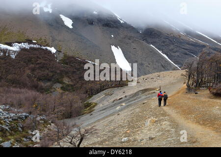 Hikers walking on a trail from the base of the Paine towers, Torres del Paine, Patagonia, Chile, South America - Stock Photo