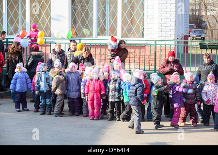 ST.PETERSBURG, RUSSIA - CIRCA FEB, 2014: Group of little kids stands with nursery school teacher in inner yard. - Stock Photo