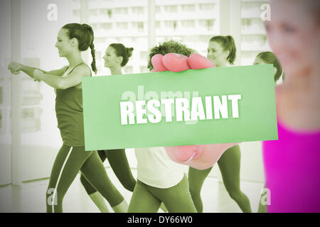 Fit blonde holding card saying restraint - Stock Photo