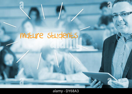 Mature students against lecturer standing in front of his class in lecture hall - Stock Photo