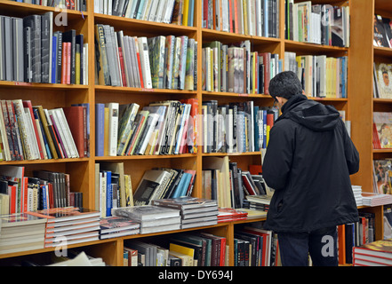 A man in a coat shopping for books at the Strand Bookstore on Broadway in Greenwich Village, Manhattan, NYC. - Stock Photo