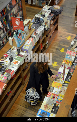 A woman shopping for books at the Strand Bookstore on Broadway in Greenwich Village, Manhattan, New York City. - Stock Photo