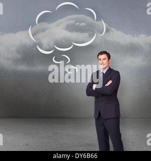 Composite image of young businessman standing cross-armed with speech bubble - Stock Photo