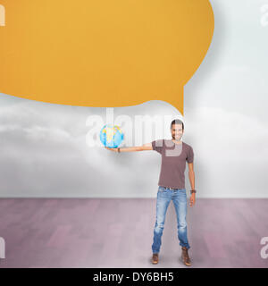 Composite image of handsome man holding out a globe with speech bubble - Stock Photo
