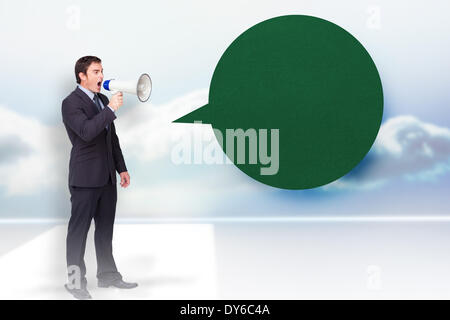 Composite image of standing businessman shouting through a megaphone with speech bubble - Stock Photo