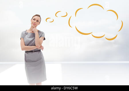 Composite image of thoughtful woman posing in dress  with thought bubble - Stock Photo