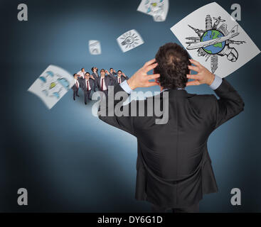 Composite image of stressed businessman with hands on head with tiny businessmen - Stock Photo